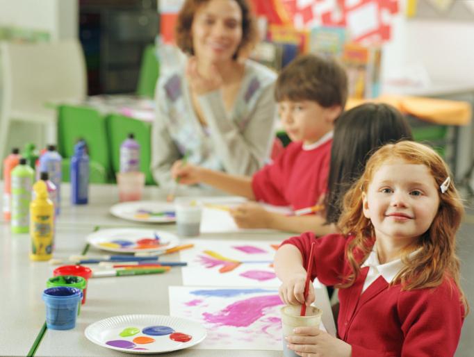 Teacher with children (5-7) using paints, girl (4-6) smiling, portrait